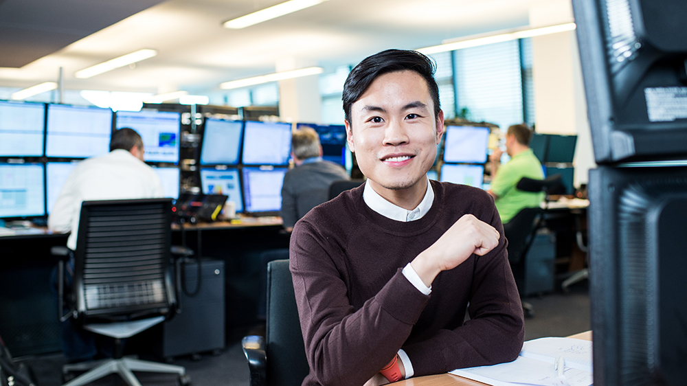 Smiling man sitting in front of trading floor